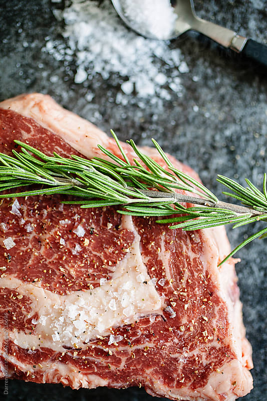 Closeup of a rib-eye steak, fat and marbling with a sprig of rosemary. by Darren Muir for Stocksy United