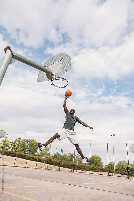 Young Black Man Playing in a Street Basketball Court by VICTOR TORRES for Stocksy United