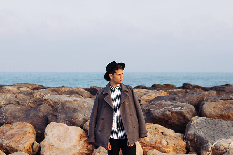 Portrait of young man on the beach with style by Susana Ramírez for Stocksy United
