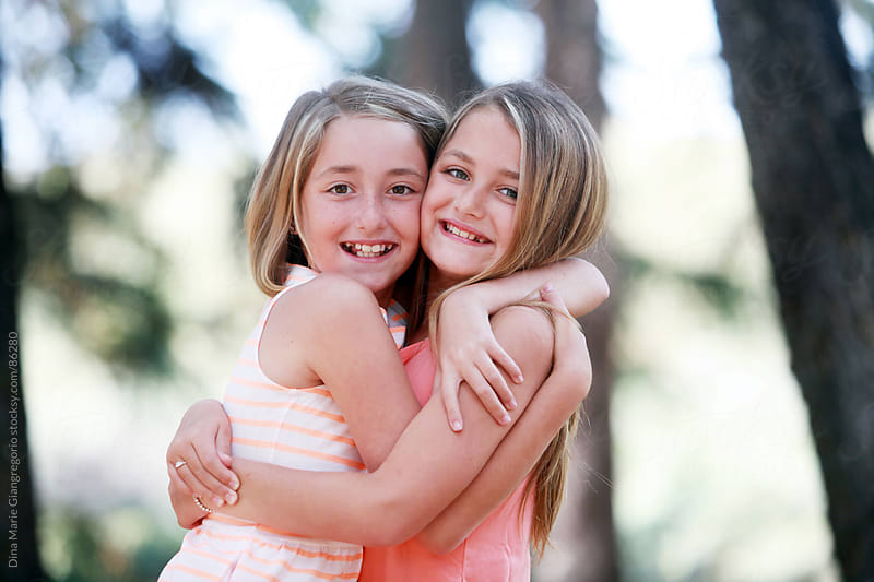 Twin Sisters Hugging Eachother Outdoors by Dina Giangregorio for Stocksy United
