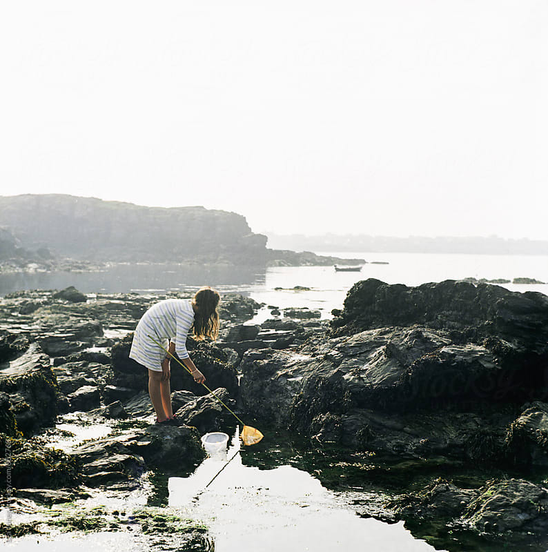 young girl fishing with a net by Léa Jones for Stocksy United