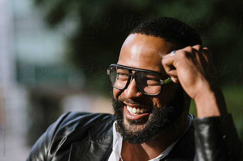 Smiling happy bearded black man outdoors by Cameron Whitman for Stocksy United
