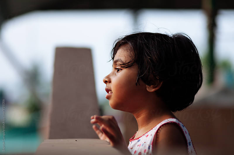 Little girl peeking over a wall  by Saptak Ganguly for Stocksy United