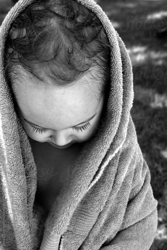 Toddler With Wet Curly Hair Wrapped In Towel Looking Down by Dina Giangregorio for Stocksy United