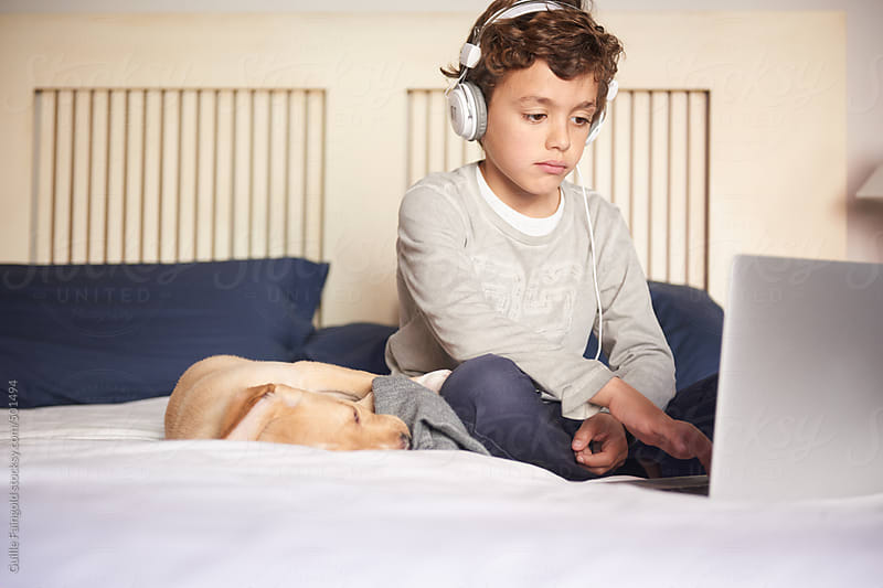 Young boy using the laptop and playing with their puppy by Guille Faingold for Stocksy United