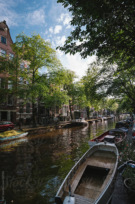 Canal with boats in Amsterdam during summer by GIC for Stocksy United