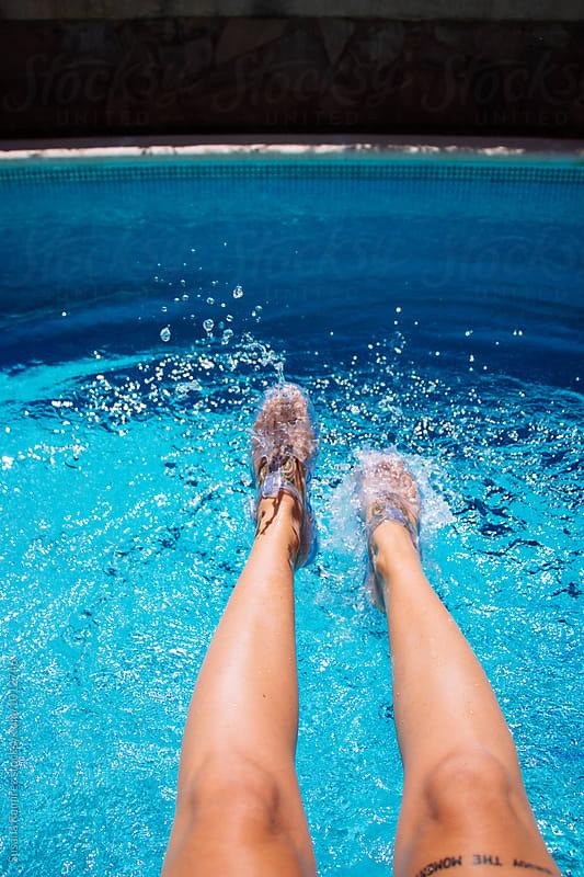Woman feet splashing in the pool by Susana Ramírez for Stocksy United