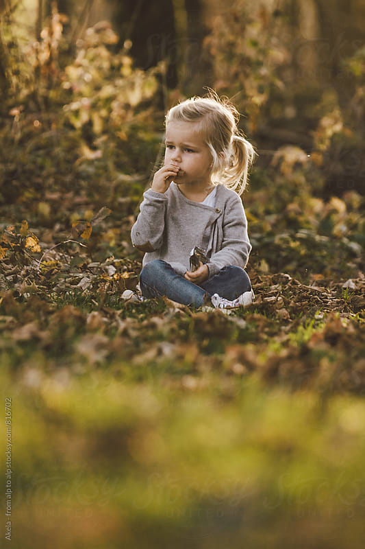 cute little girl sitting in foliage covered forest eating sweets by Leander Nardin for Stocksy United