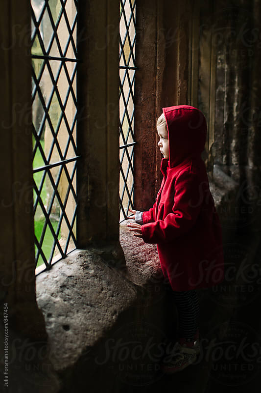 Little girl in a red coat looks out of a window in a cathedral cloister. by Julia Forsman for Stocksy United