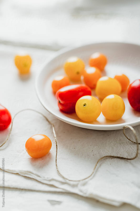 Yellow, orange and red cherry tomato by Tatjana Ristanic for Stocksy United