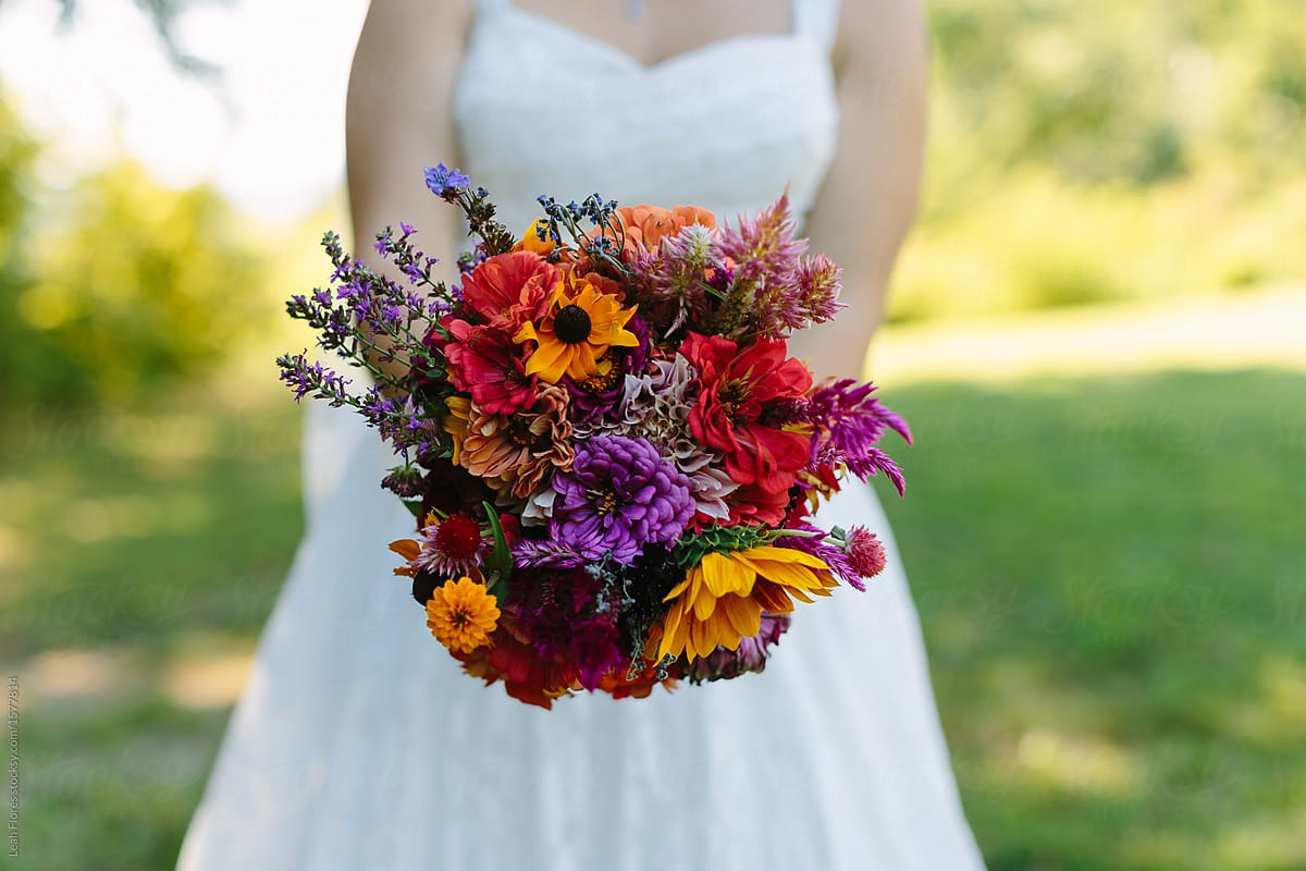 Bride holding colorful wildflower bouquet stocksy united bride holding colorful wildflower bouquet by leah flores for stocksy united izmirmasajfo