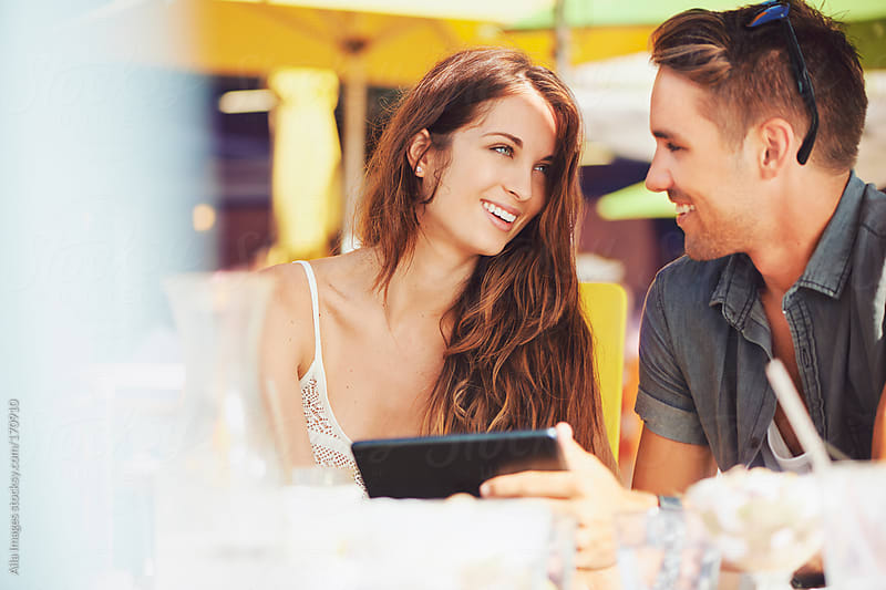 Couple using digital Tablet at cafe by Aila Images for Stocksy United