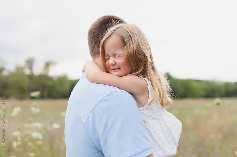 A young daughter squeezes father's neck, embrace by Amanda Worrall for Stocksy United