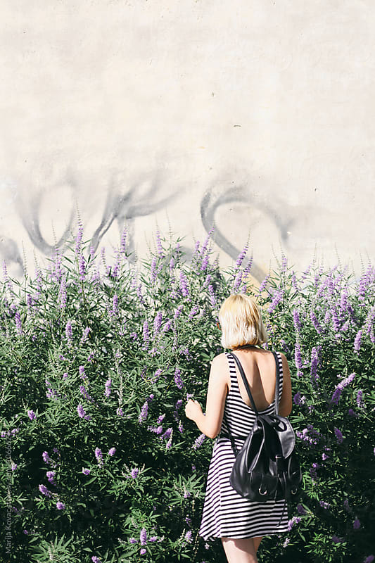 Blonde woman from behind, next to the purple flowers by Marija Kovac for Stocksy United