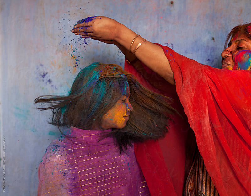 Mother givinf colorful spray powder to her daughter during Holi festival by PARTHA PAL for Stocksy United