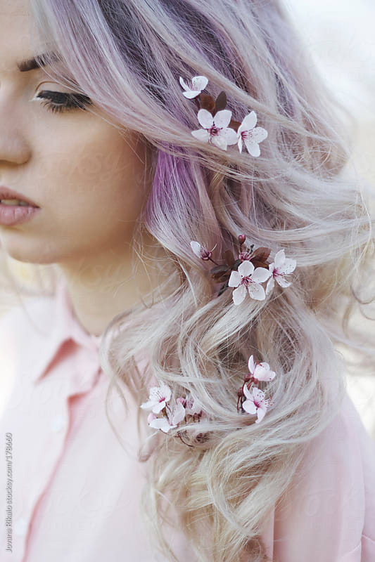 Young woman with flowers in her hair by Jovana Rikalo for Stocksy United