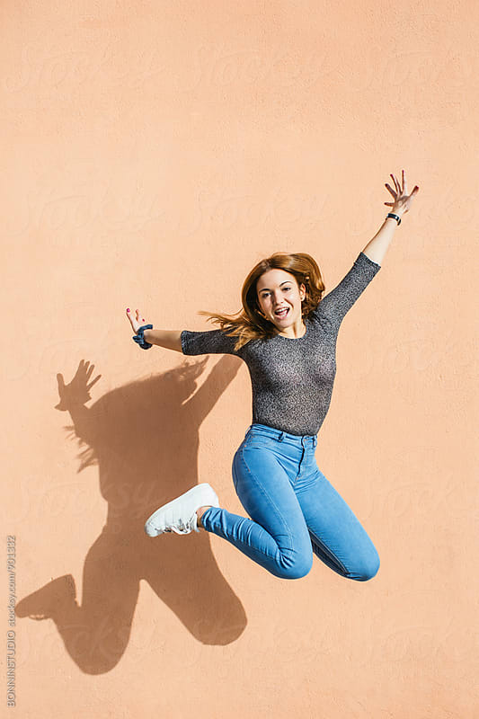 Happy girl jumping in front of a wall outside. by BONNINSTUDIO for Stocksy United