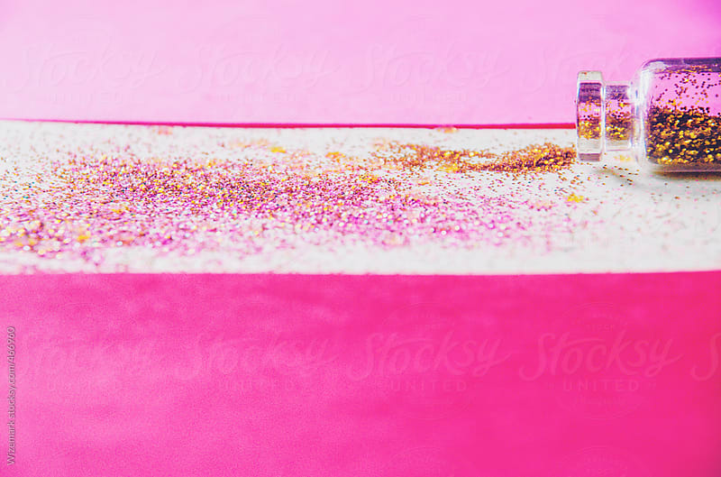 Shiny glitter spilled on the table from a tiny glass bottle by Wizemark for Stocksy United