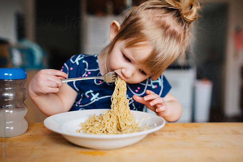Cute toddler girl in blue dress eating ramen noodles at the kitchen table. by Jessica Byrum for Stocksy United