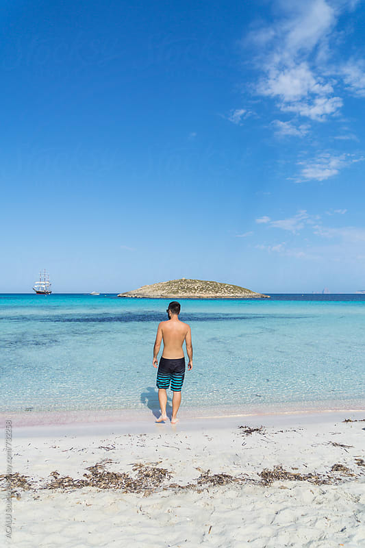Young man walking in a paradise beach by ACALU Studio for Stocksy United