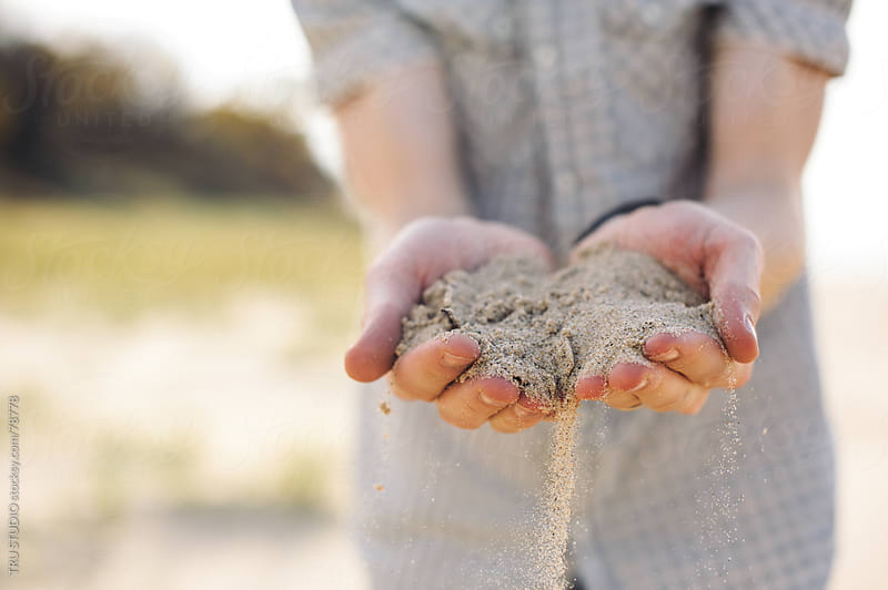 Young man holding sand in hands on beach by TRU STUDIO for Stocksy United