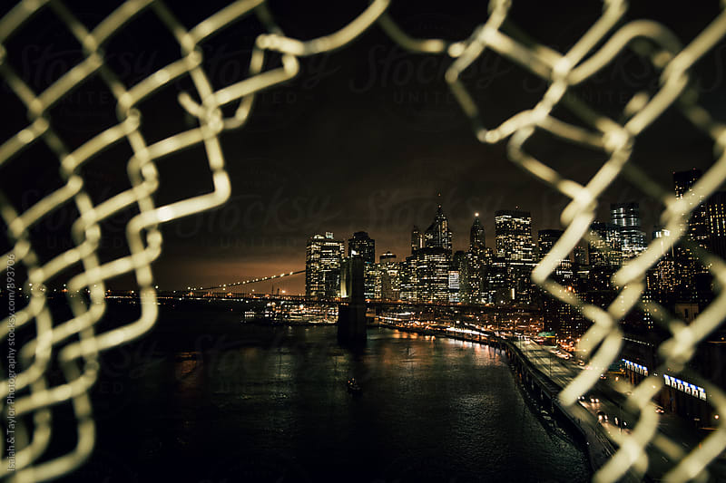City viewed through fence by Isaiah & Taylor Photography for Stocksy United