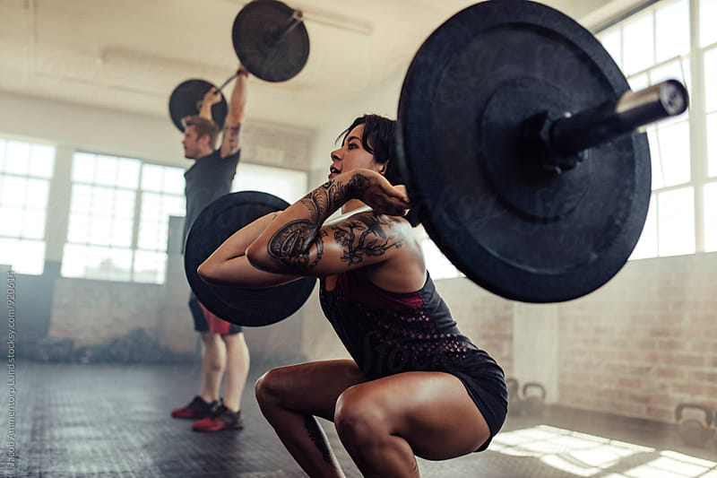 Woman doing front squats at gym by Jacob Ammentorp Lund for Stocksy United