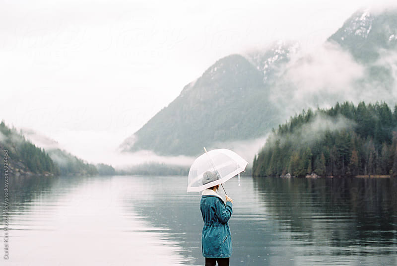 Woman standing over lake with umbrella by Daniel Kim Photography for Stocksy United