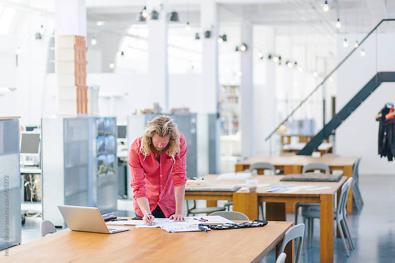 Young designer working behind a desk in spacious beautiful office or studio by Ivo de Bruijn for Stocksy United