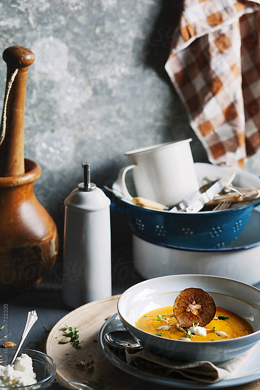 A serving of squash soup in a blue bowl within a rustic table setting. by Darren Muir for Stocksy United