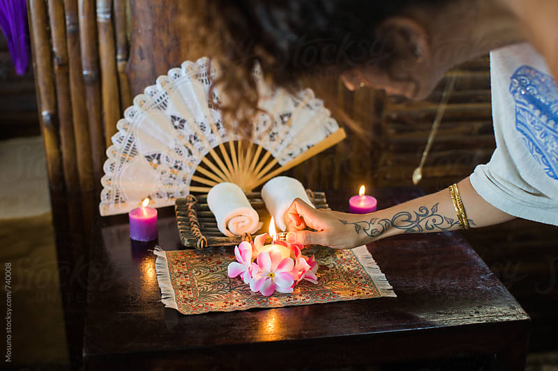 Woman Lighting a Candle by Mosuno for Stocksy United