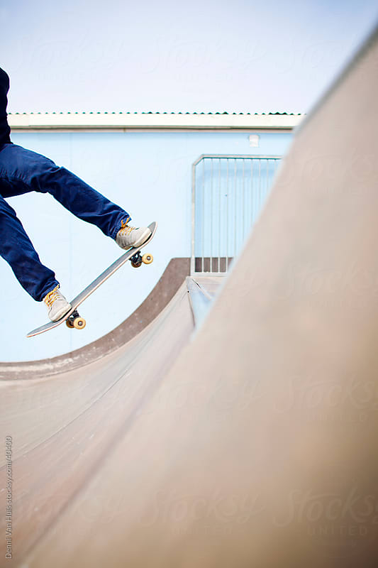 Young man landing a skateboard trick in a skate park on a sunny day by Denni Van Huis for Stocksy United