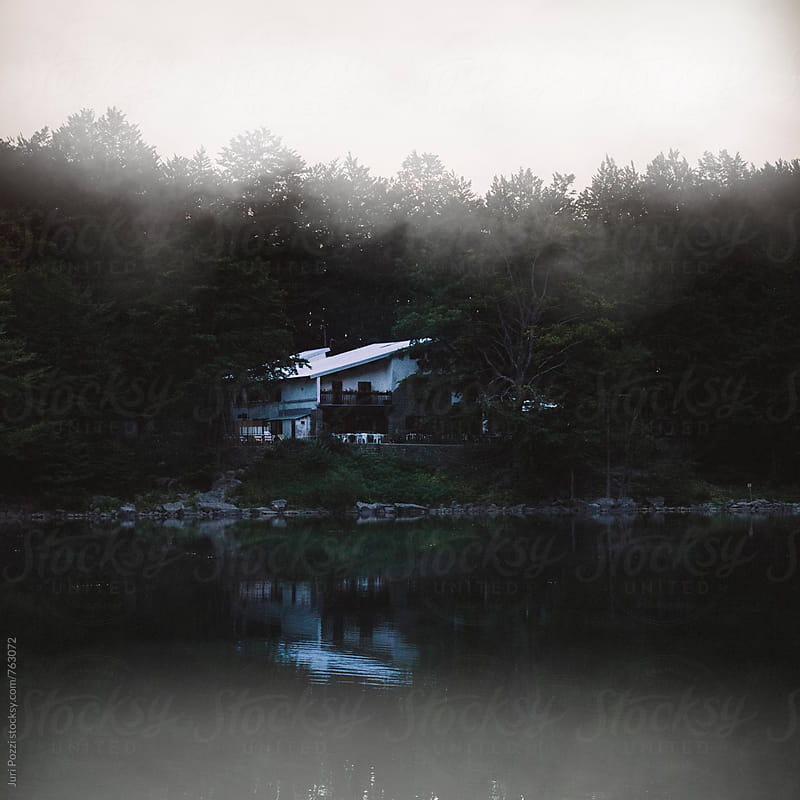housing in front a lake in a foggy morning by Juri Pozzi for Stocksy United