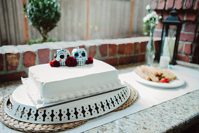 White cake decorated with spanish skulls by Kristine Weilert for Stocksy United