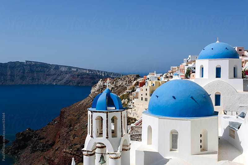 The blue domes and bell tower of churches in Oia, Santorini by Paul Phillips for Stocksy United
