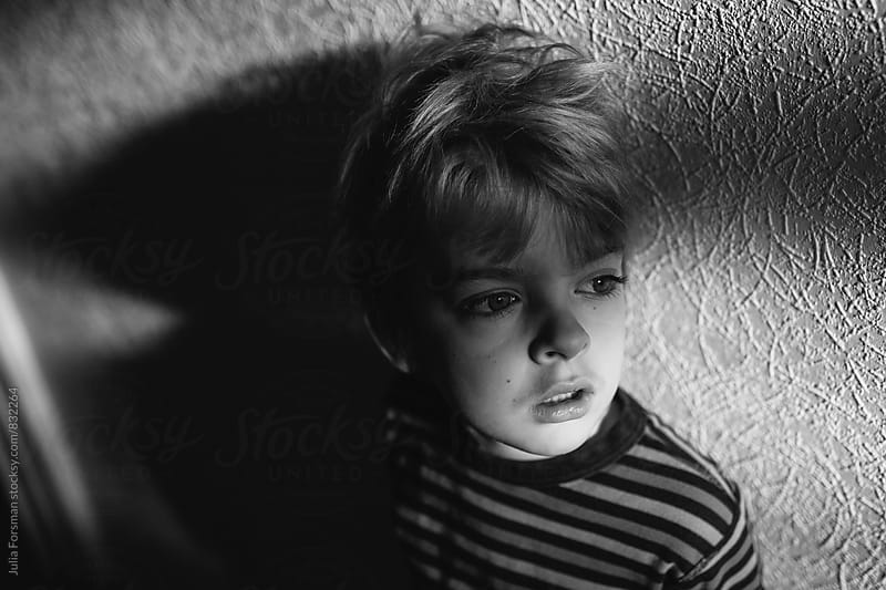 Young boy looking towards light with shadows behind him. by Julia Forsman for Stocksy United