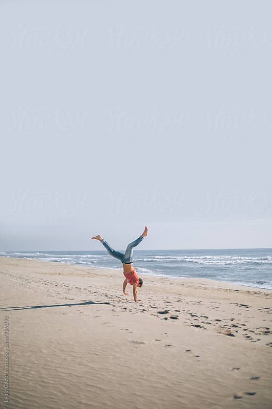 Young man jumping along the beach because he's happy by Lydia Cazorla for Stocksy United