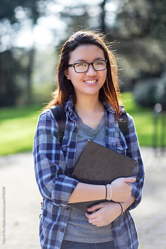 Asian college student carrying a book on campus by Suprijono Suharjoto for Stocksy United