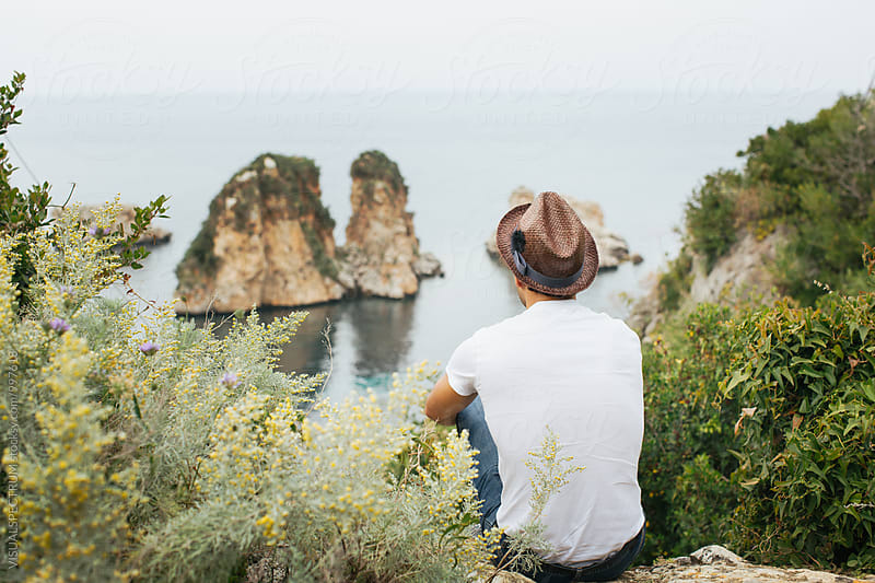 Young Man With Brown Straw Hat Sitting by Ocean and Looking at Sea by Julien L. Balmer for Stocksy United