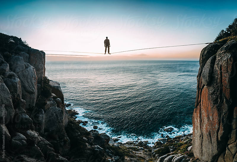 Man tight rope walking on a high line looking out to sunset over the sea by Micky Wiswedel for Stocksy United