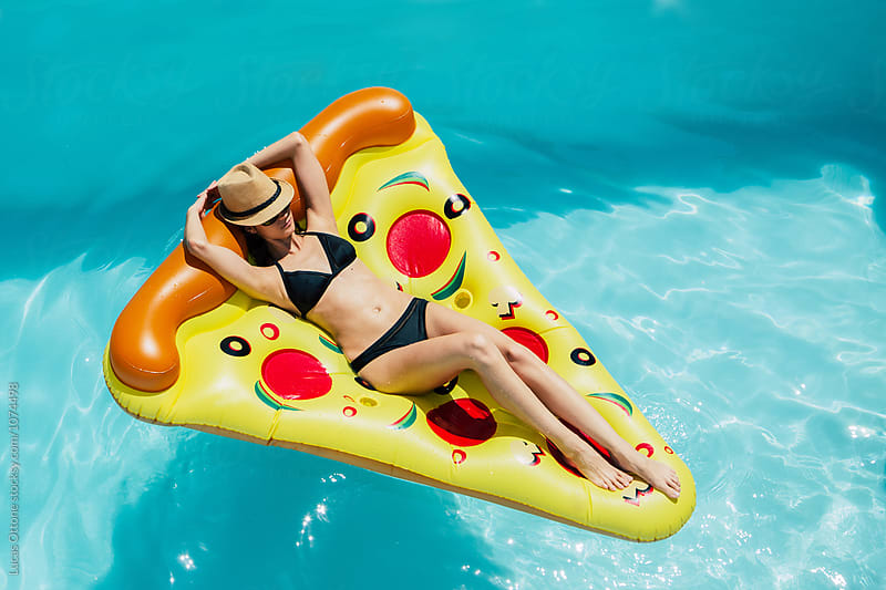 Woman on a pizza float in a swimming pool by Lucas Ottone for Stocksy United