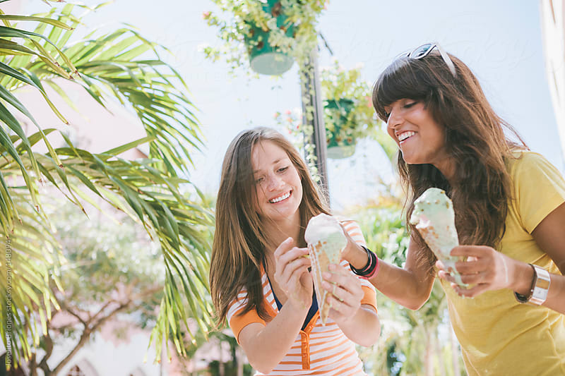Two Young Women Students Eating Ice Cream on Spring Break in South Beach Miami by Joselito Briones for Stocksy United