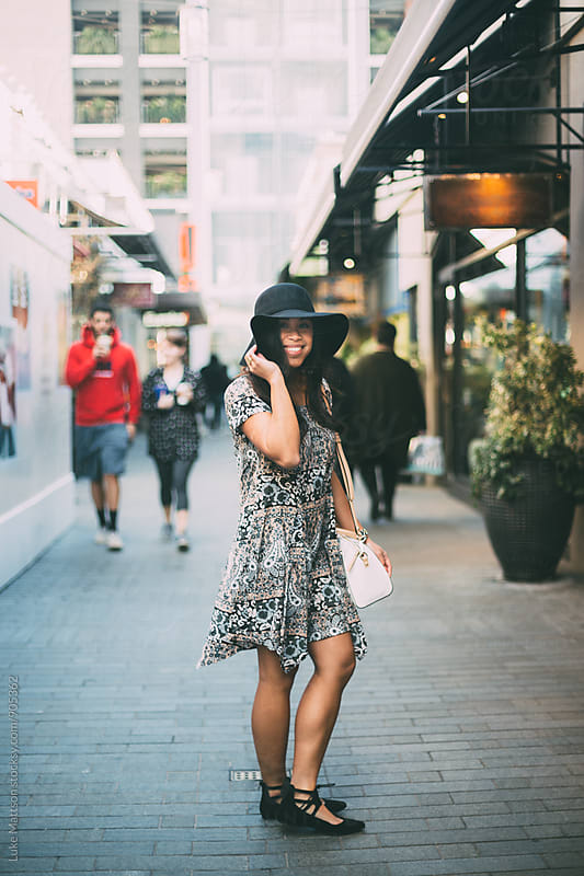 Smiling Young Woman Standing Outside Shopping Mall by Luke Mattson for Stocksy United