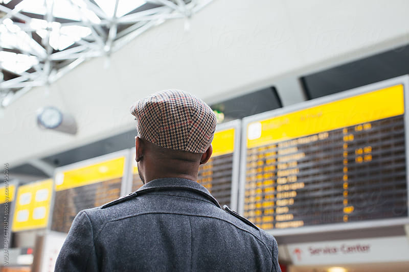 Young Black Man Looking at Arrival/Departure Board in Airport by VISUALSPECTRUM for Stocksy United