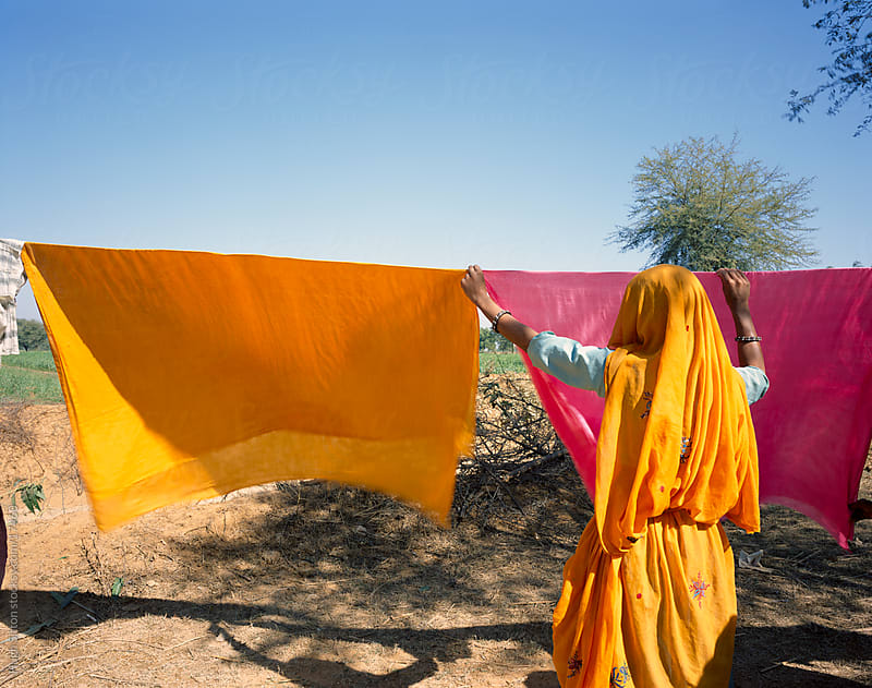 Indian woman wearing sari drying clothes. Rajasthan. India by Hugh Sitton for Stocksy United