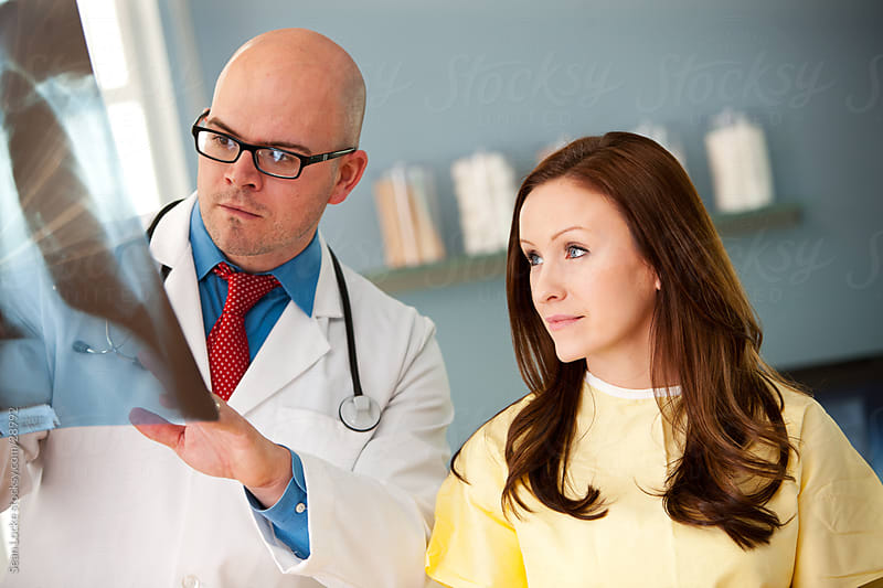 Exam Room: Doctor Discusses X-ray with Patient by Sean Locke for Stocksy United
