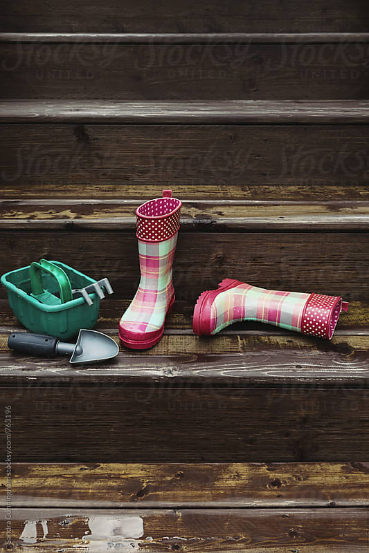 Little girl's rain boots with garden tools on stairs by Sandra Cunningham for Stocksy United