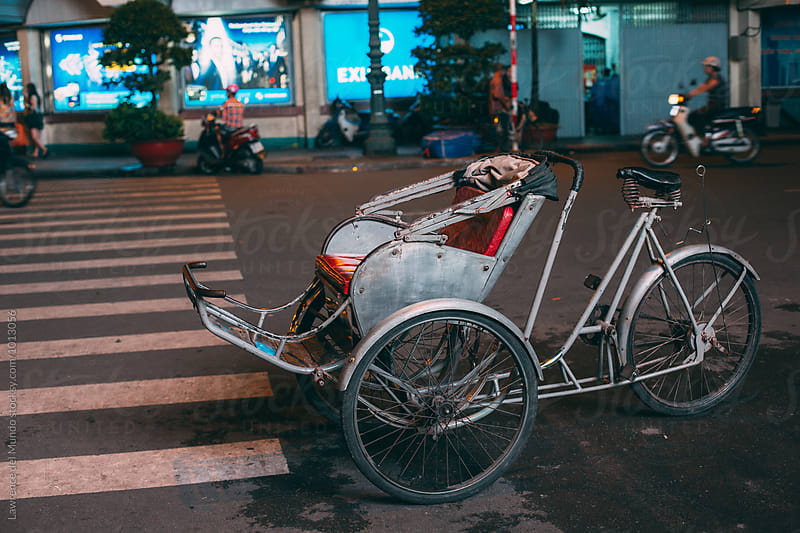 Pedal powered rickshaw on the streets of Saigon by Lawrence del Mundo for Stocksy United