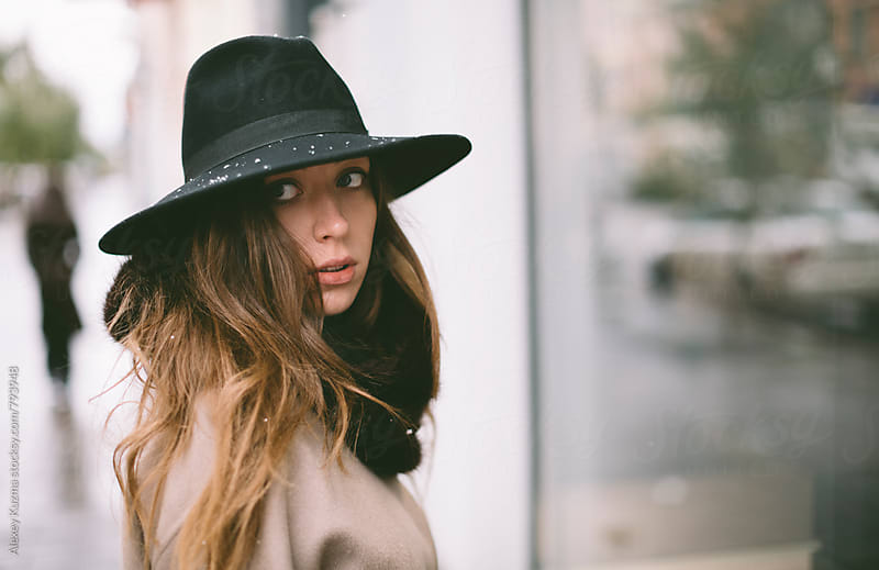 winter portrait of young woman with hat on the street  by Alexey Kuzma for Stocksy United