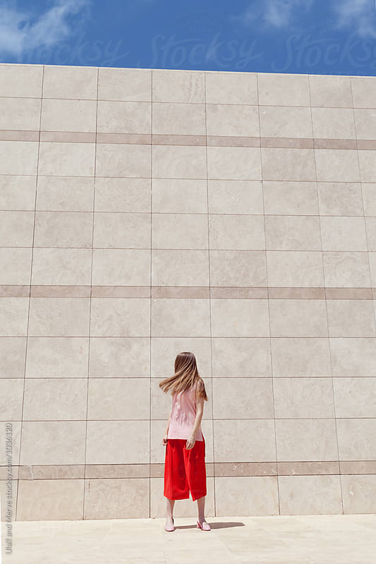 blond woman posing in front of a marble wall by Ulaş and Merve for Stocksy United